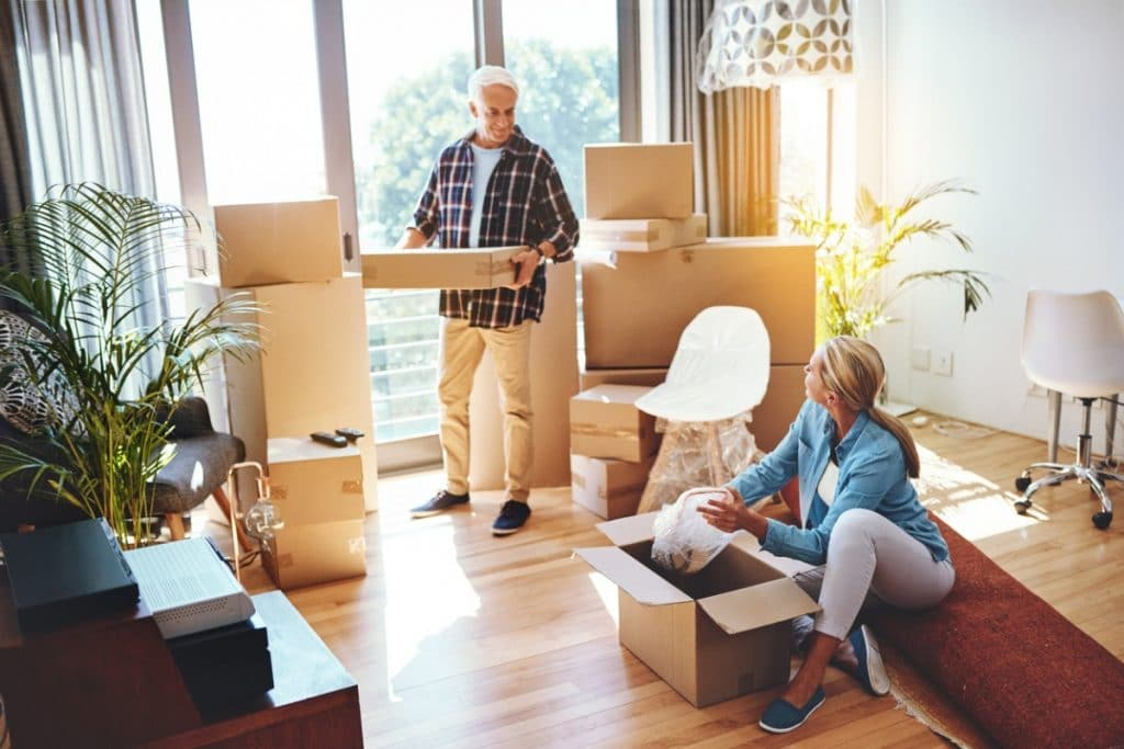 Older couple following packing tips for fragile items in their living room