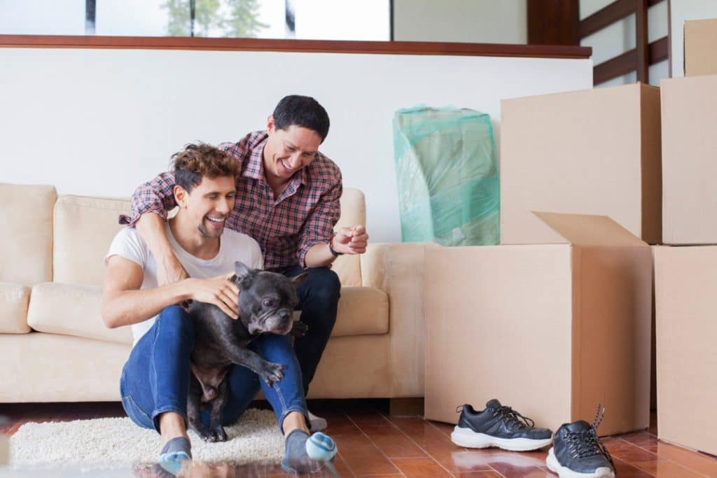 Young homosexual couple holding their small dog while sitting next to moving boxes