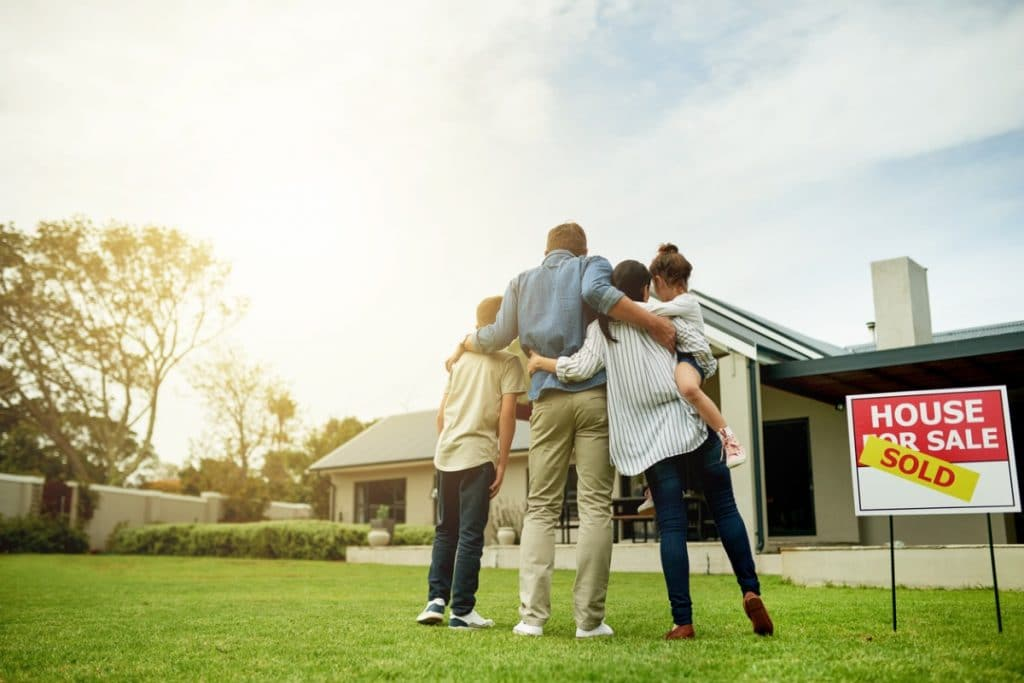 Moving with kids: a family looking at their new home from the front lawn