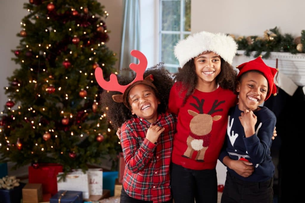 Three children wearing holiday attire, standing in front of a Christmas tree