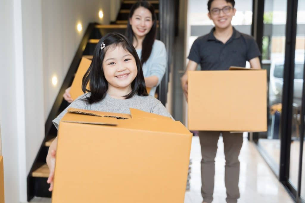Little girl holding a moving box with parents behind her