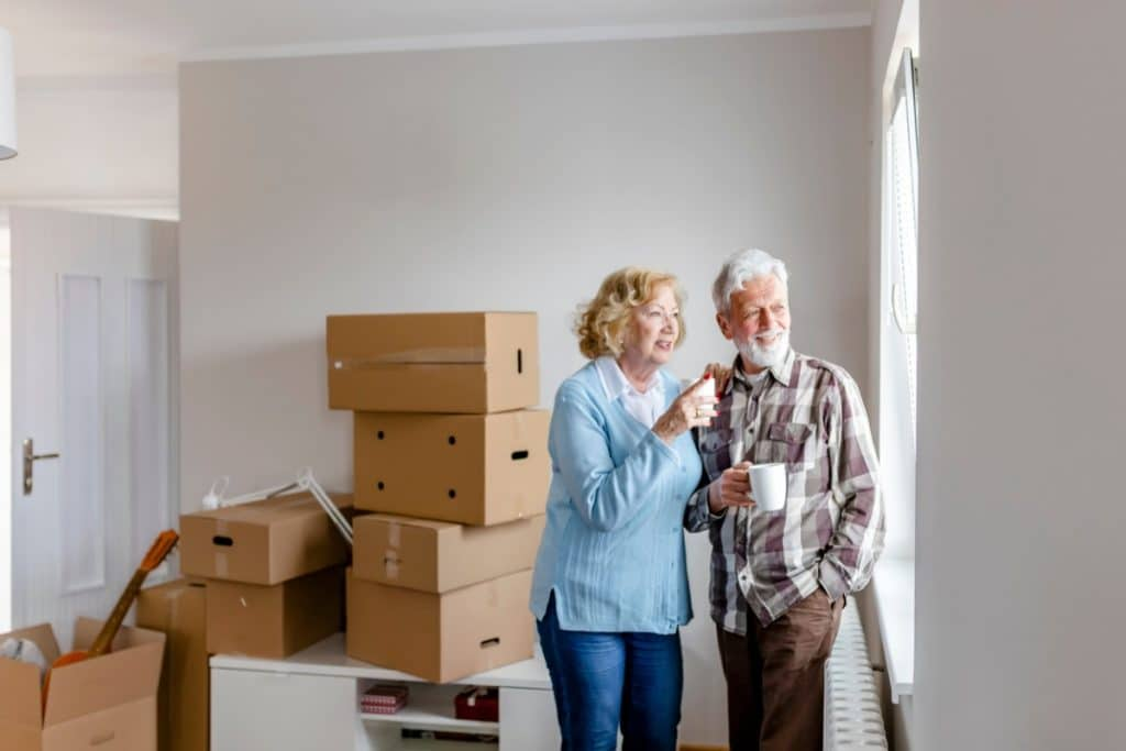 Senior couple drinking coffee and looking out the living room window while standing next to cardboard boxes on moving day
