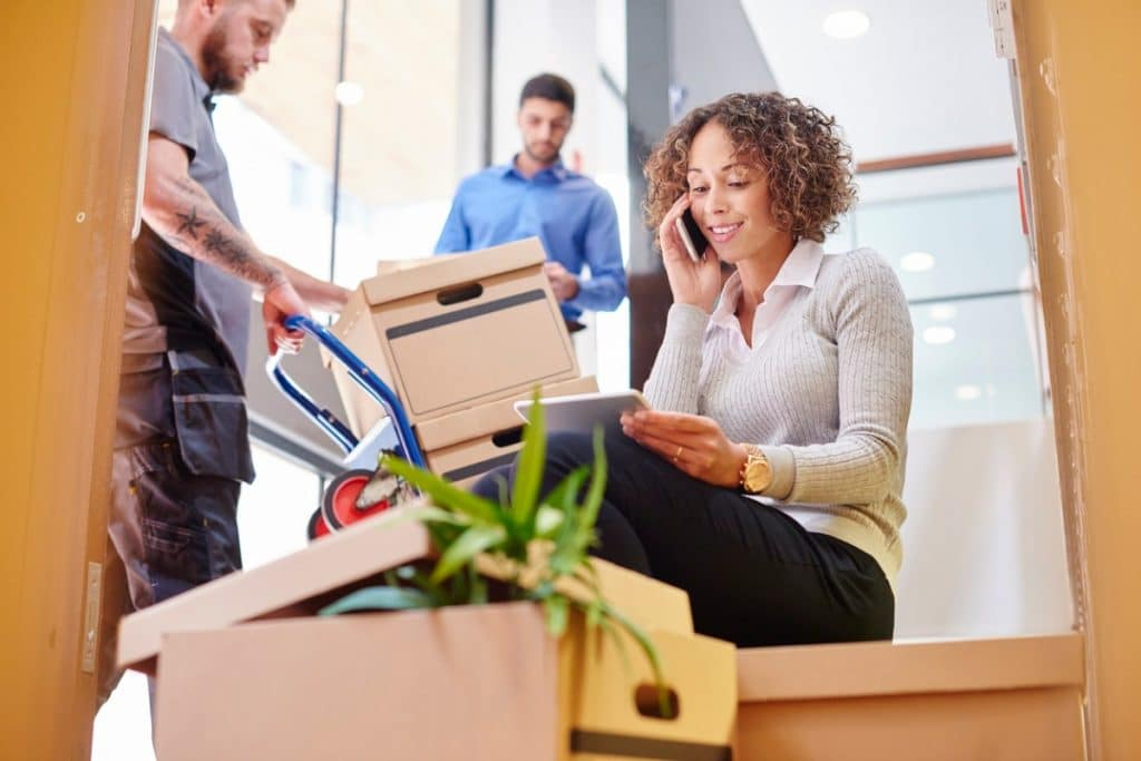 Woman on the phone at an office while two men move boxes during the unpacking process
