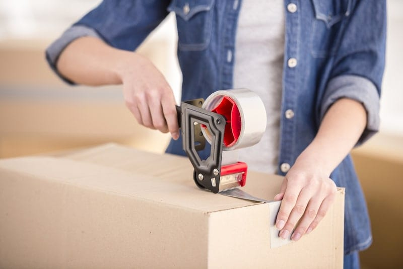 woman-in-denim-sealing-boxes-with-packaging-tape