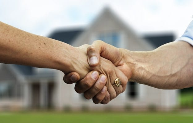 Two hands interlocked in a handshake in front of a house