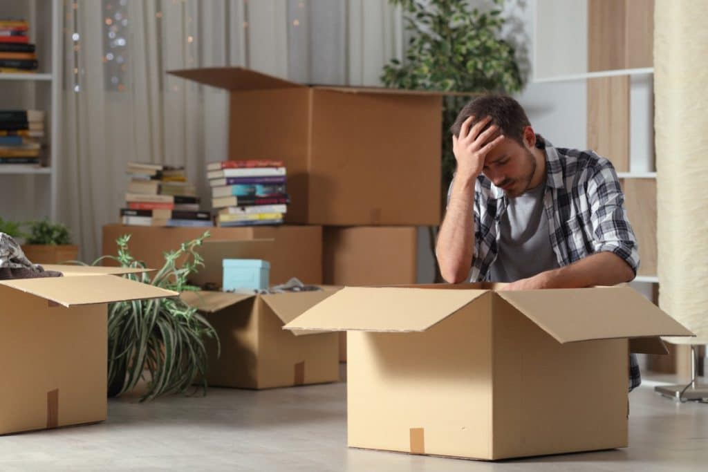 Man on the floor with head in his hand surrounded by moving boxes, experiencing anxiety about moving