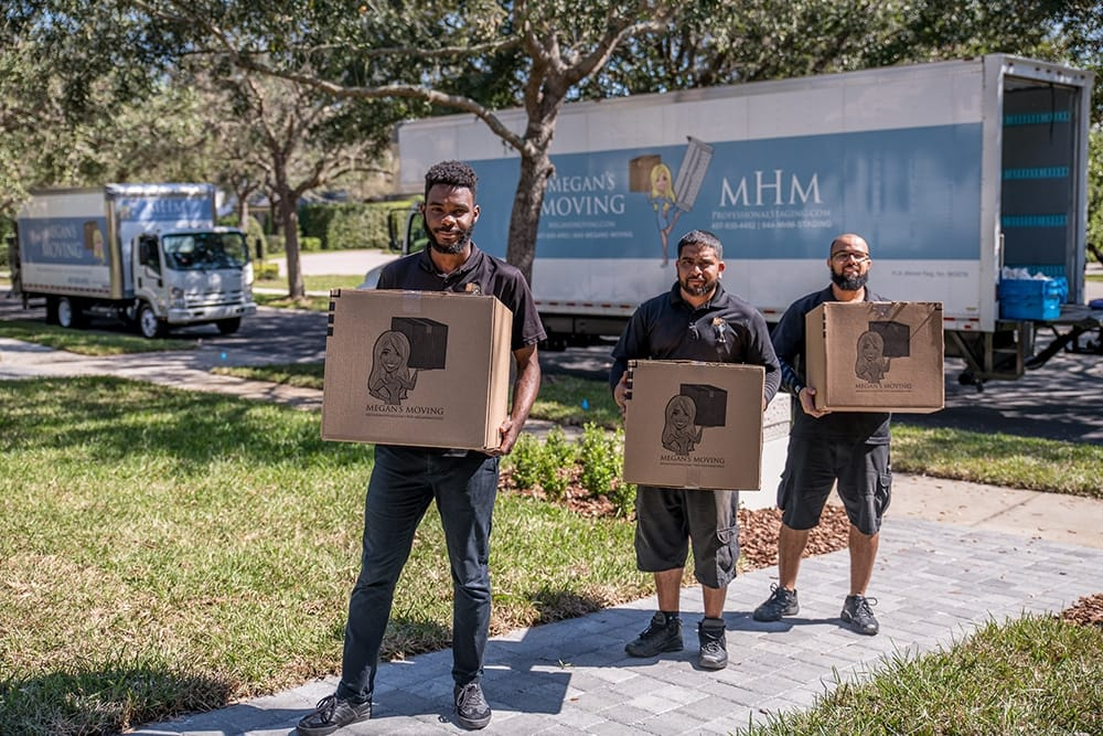 Movers from Megan's Moving carrying boxes from a moving truck