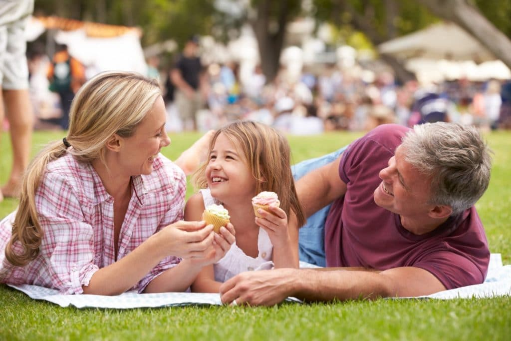Family having fun eating cupcakes in the grass at a festival