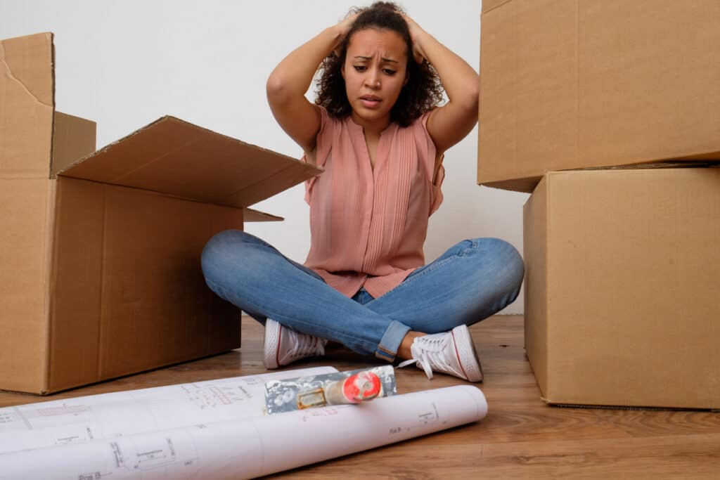 Stressed out woman sitting on the floor and packing for a move