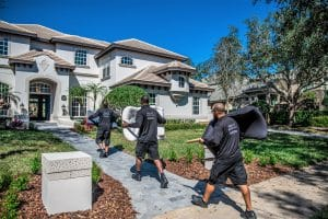 Megan's Moving crew carrying chairs into a large home