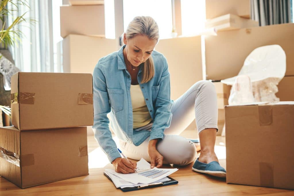 A woman reviewing a bill of lading (BOL) while sitting on the floor surrounded by moving boxes.
