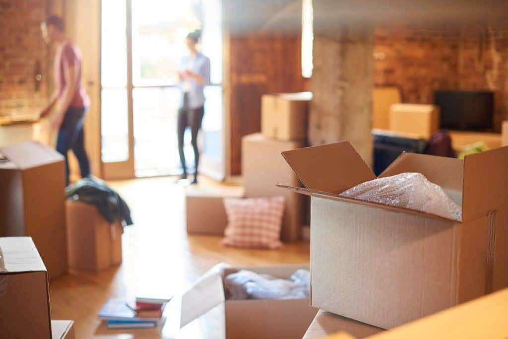Open boxes and a young couple packing, one of three things to avoid when moving