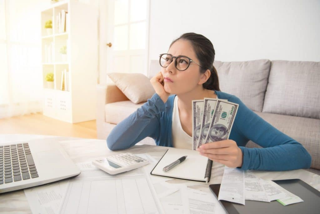 Woman sitting at a computer, holding cash, and thinking about her moving budget