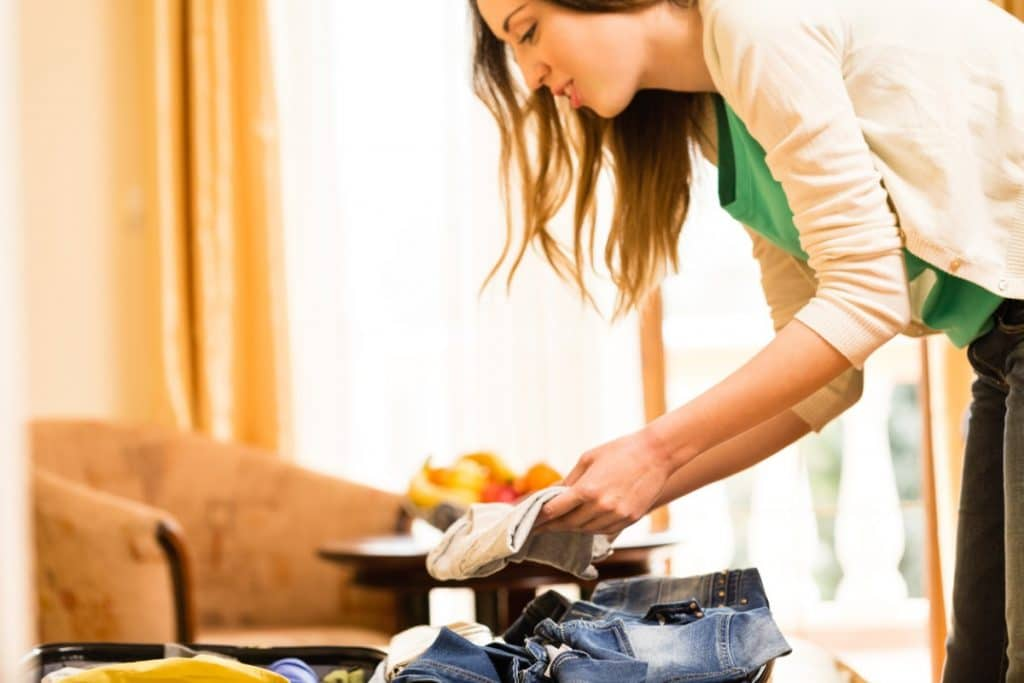 Young woman packing clothes