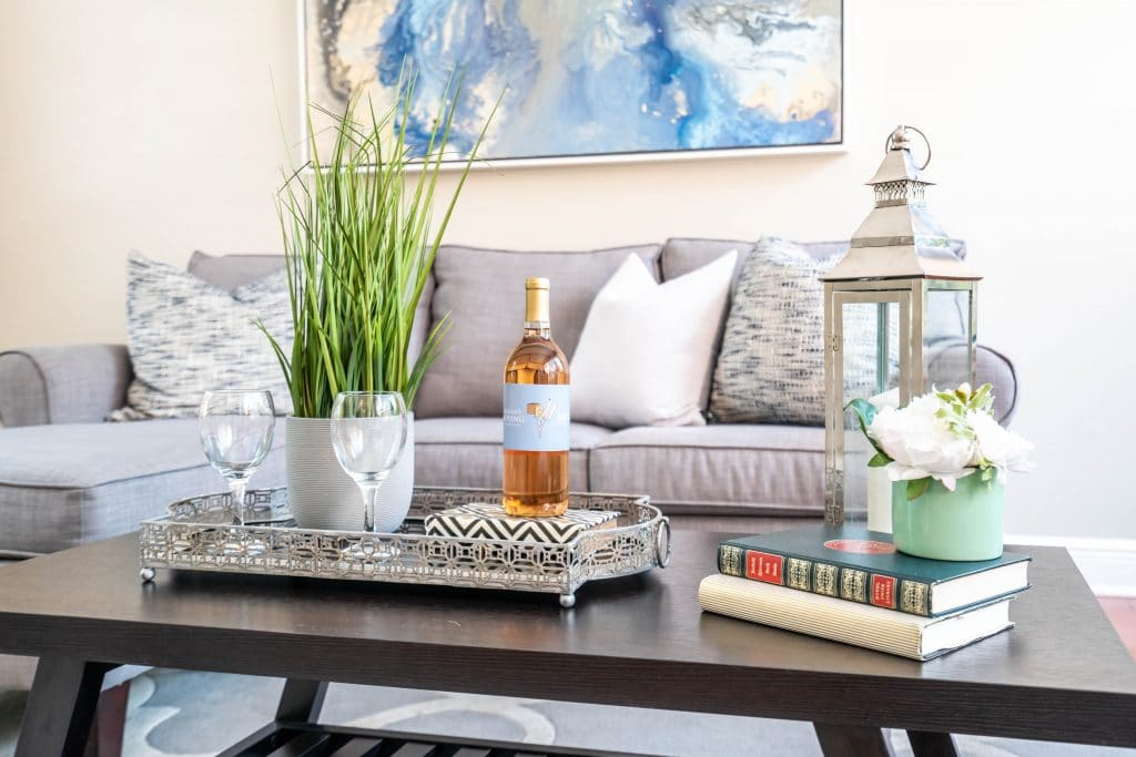 Coffee table staged with a plant, wine bottle, and wine glasses