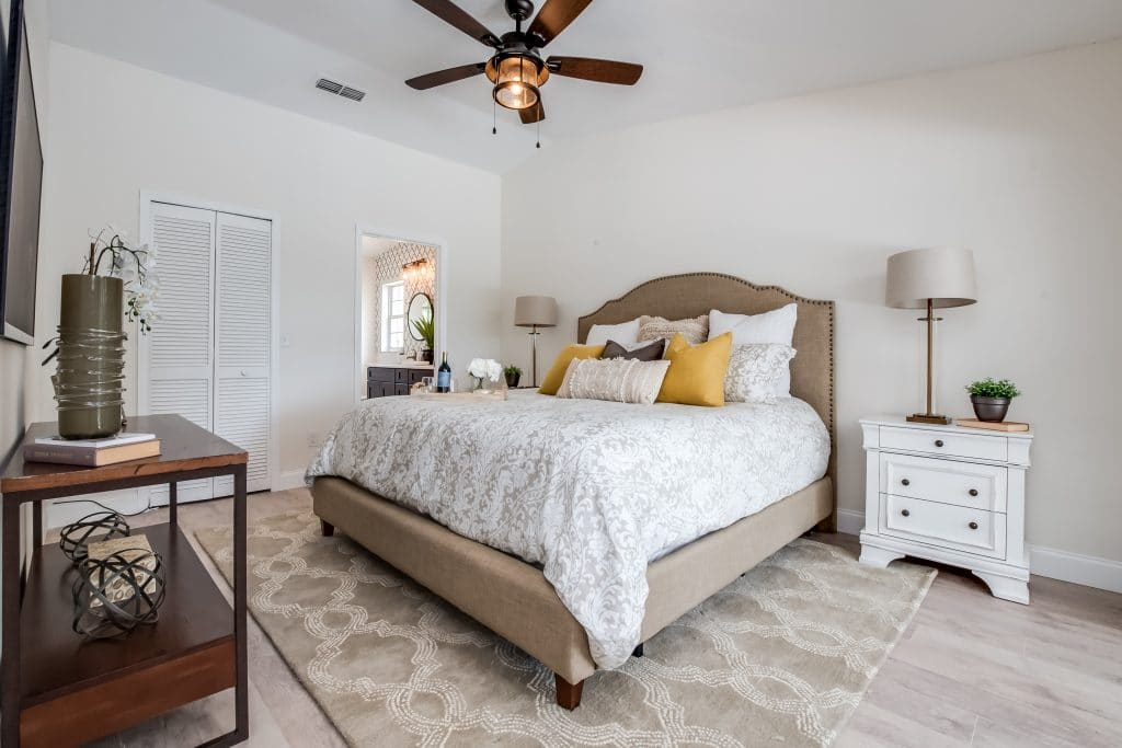 Bedroom staged with a bed, console table, and nightstands