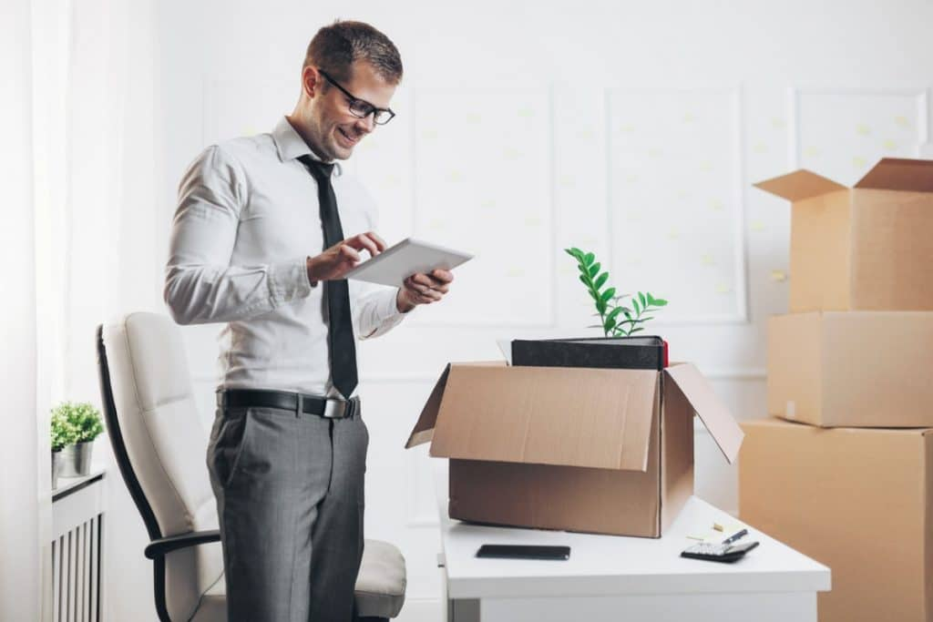 Businessman researching moving companies on a tablet computer