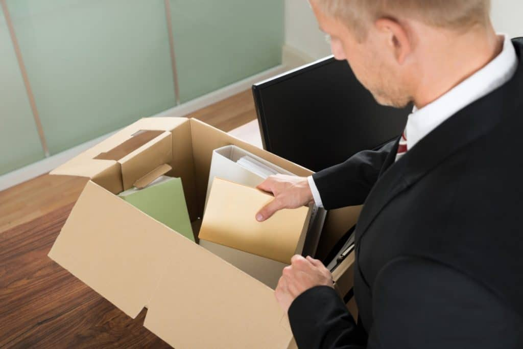 Man in a suit packing a box of office supplies on top of his desk