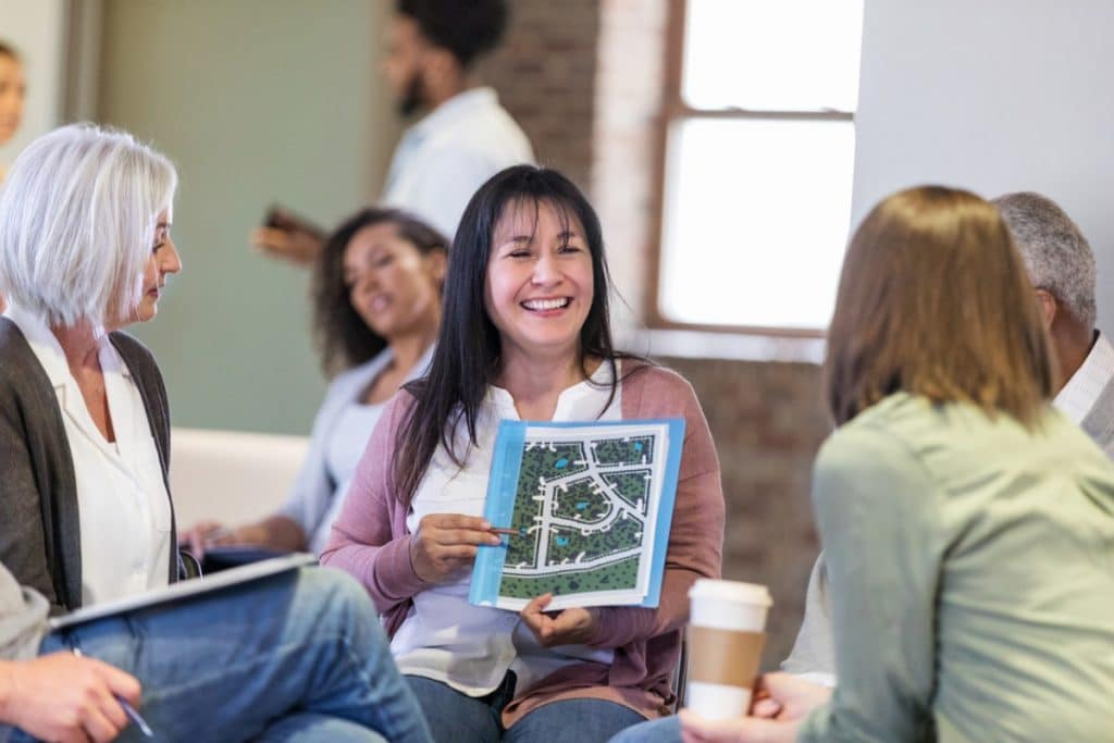 Woman showing a diagram of walking paths at an HOA meeting