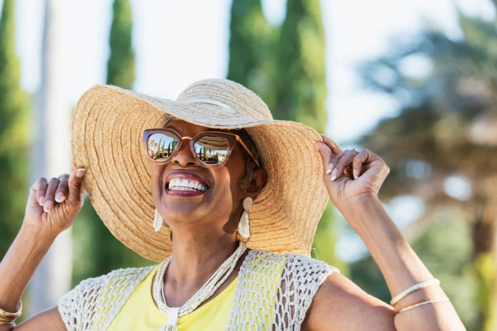 African American woman smiling while wearing a hat and sunglasses