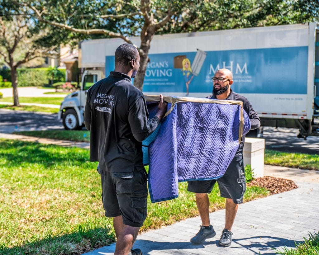 African American and Hispanic members of Megan's Moving team moving something into a home.