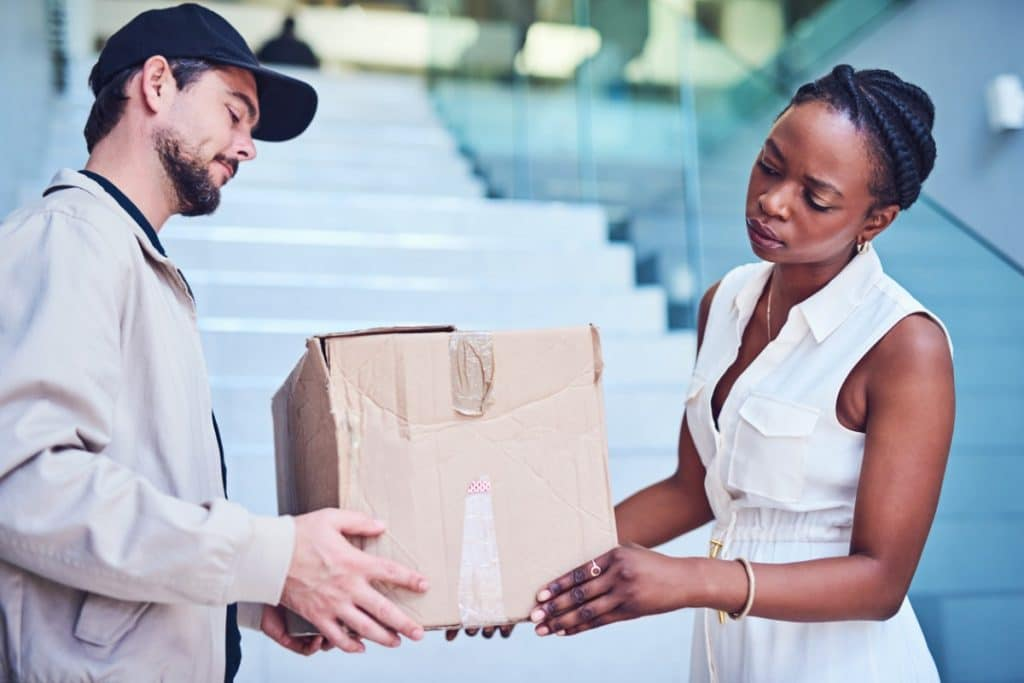 Man handing a woman a crushed box that probably has a low ECT rating