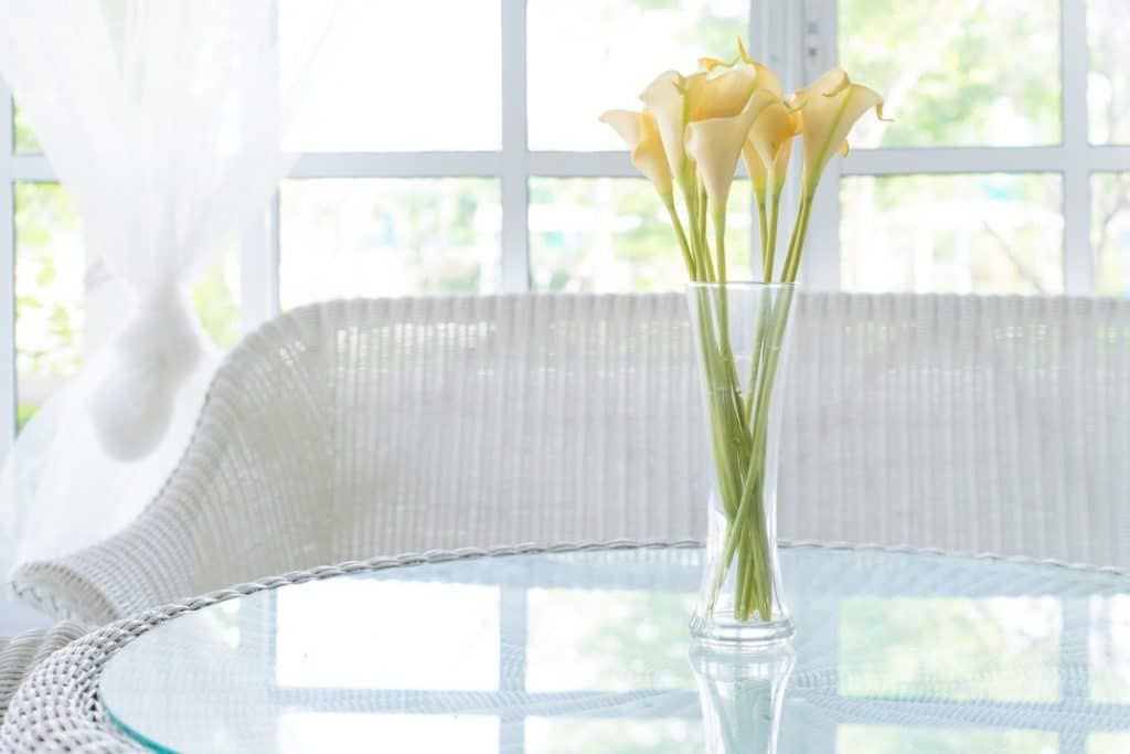 Glass-top table with white wicker bench and a vase of flowers