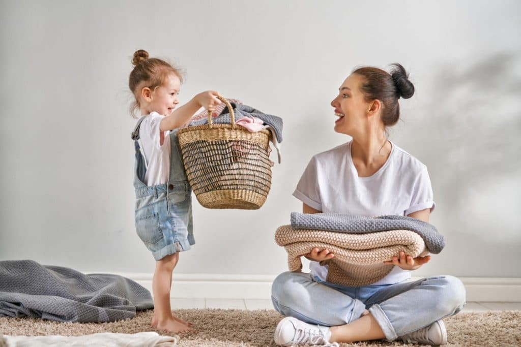 Mom and child tidying towels together