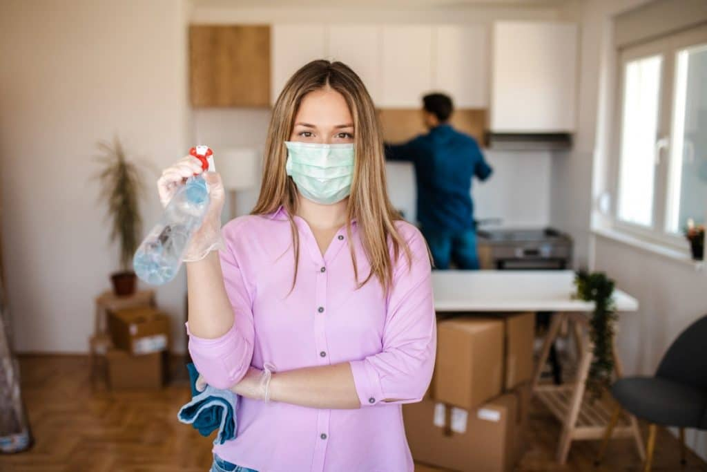 Woman in a mask cleaning her house during coronavirus outbreak to prepare for a move