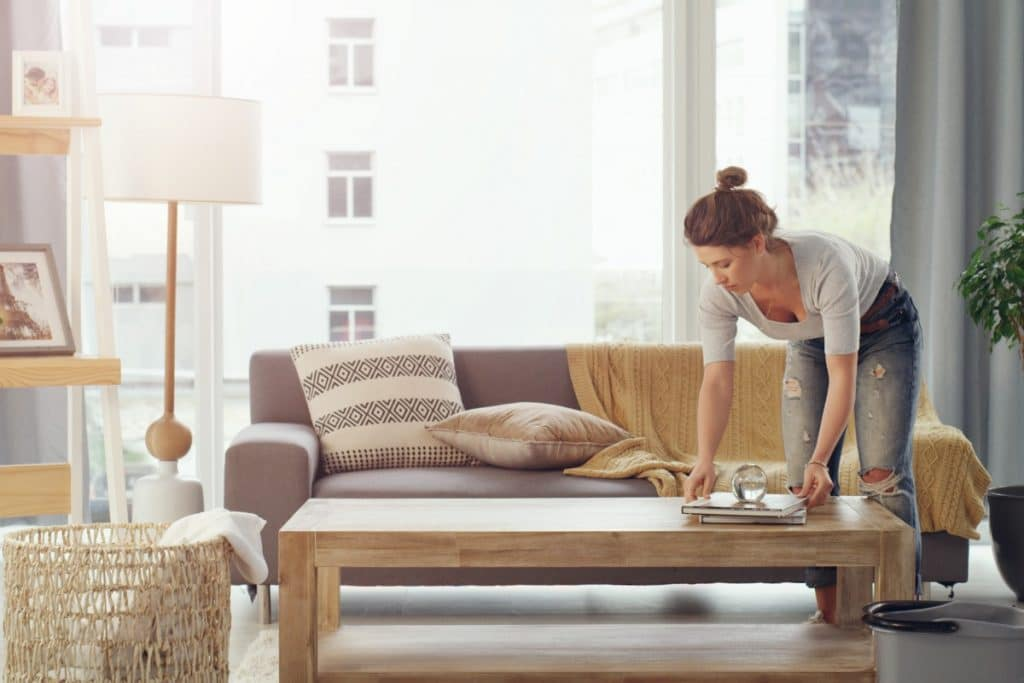 Woman tidying a coffee table in her living room