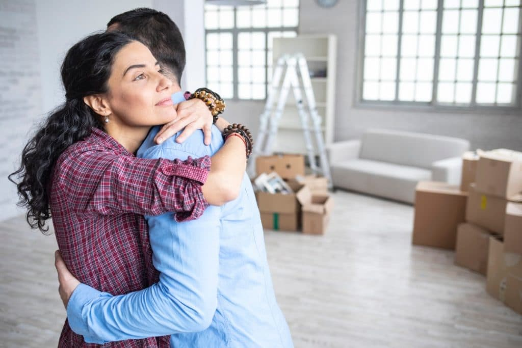 Couple embracing while standing next to moving boxes