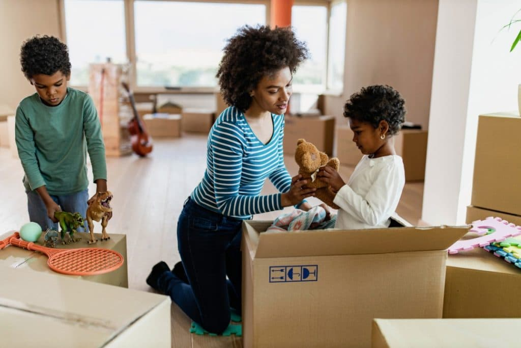 Mom helping kids pack stuff animals for a move
