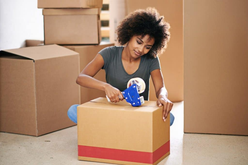Young African-American woman taping up moving boxes of various sizes.