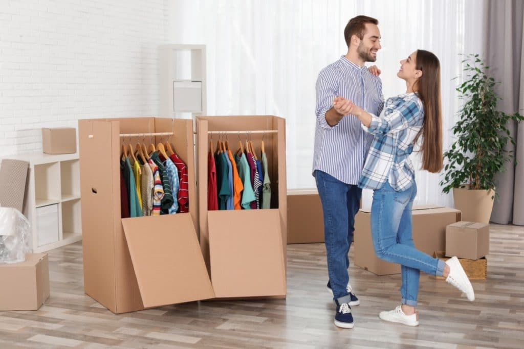 Couple standing next to two wardrobe boxes full of clothes on hangers