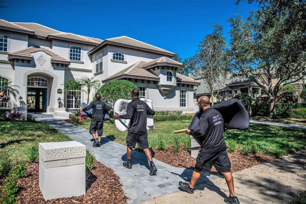 Megan's Moving professional movers carrying furniture into a large luxury home.