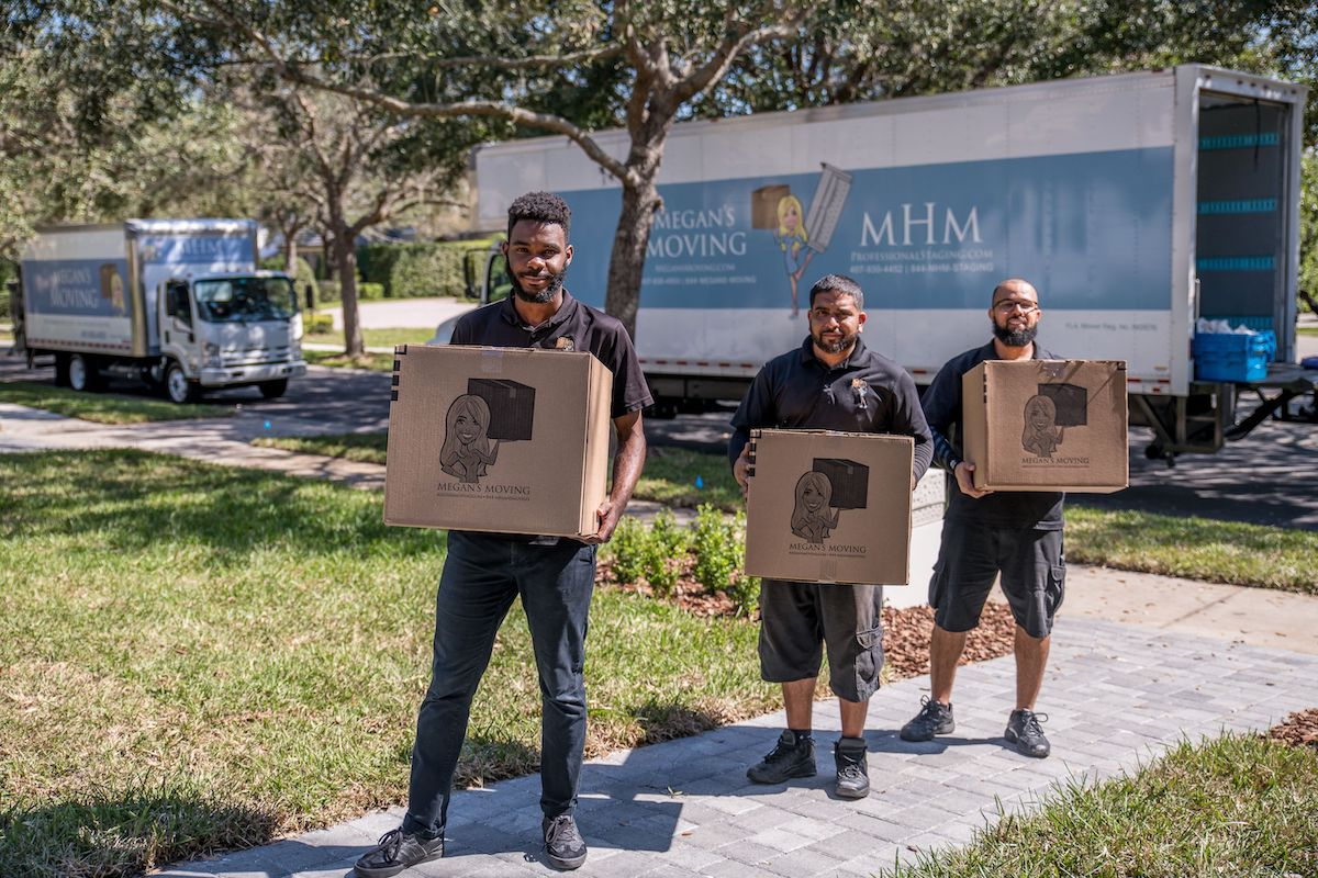Megan's Moving team carrying moving boxes with the moving truck in the background.