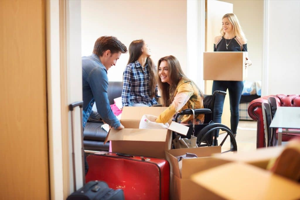 Young woman in a wheelchair packing boxes with her friends