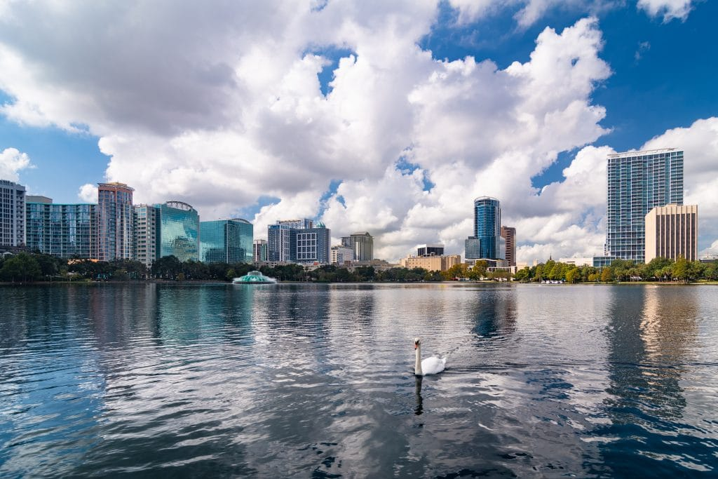 Photo of Lake Eola in the foreground with Downtown Orlando's tall buildings in the background.