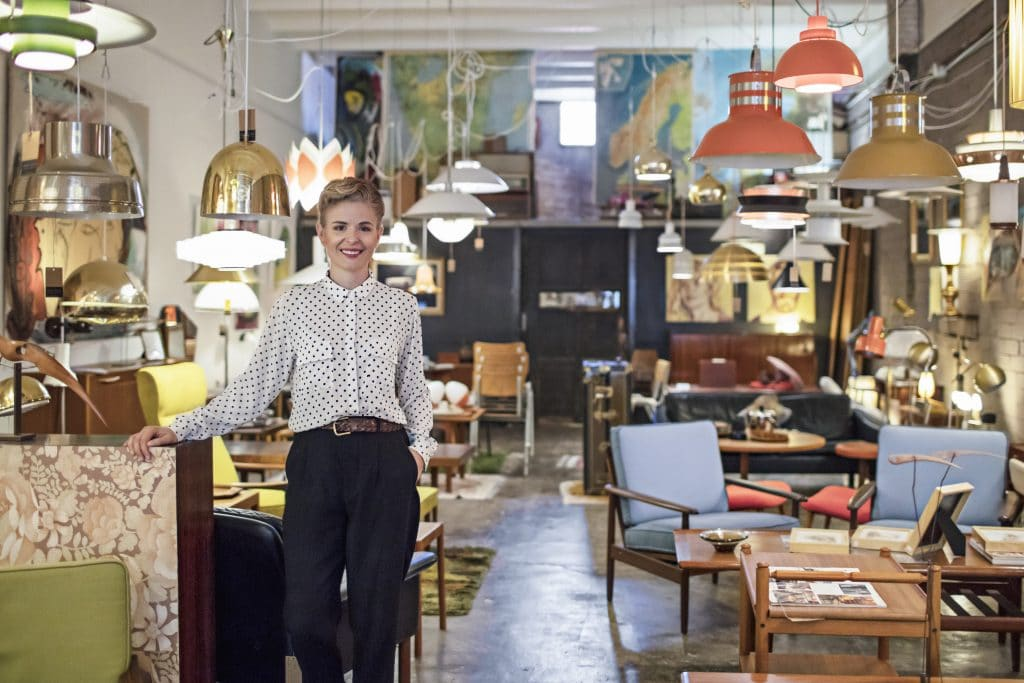 A woman standing in an antique furniture shop.
