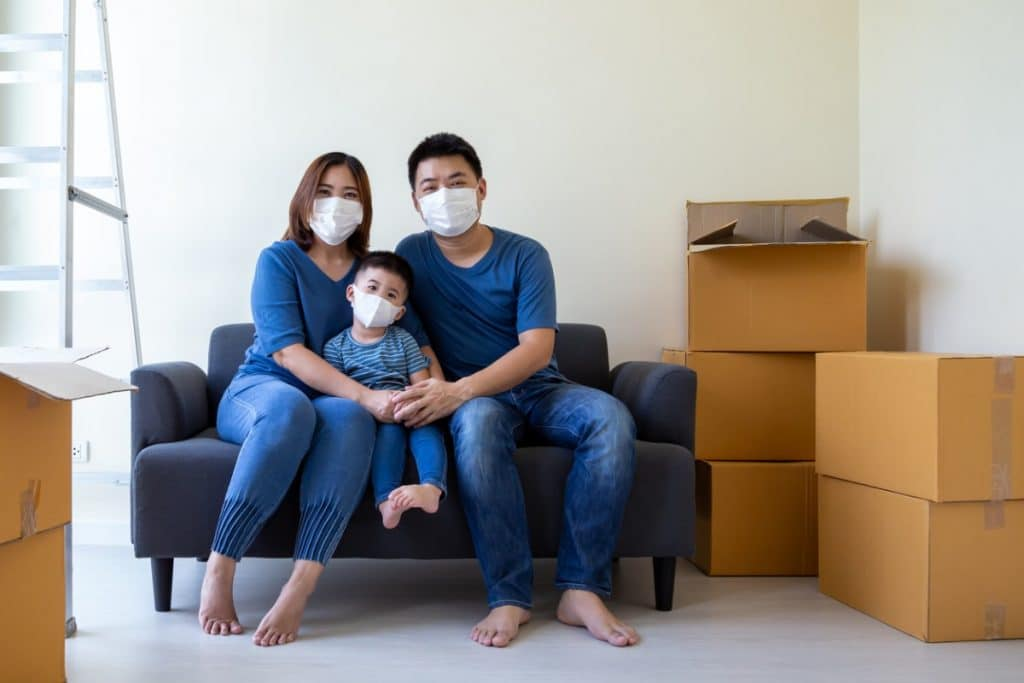 Asian family wearing face masks while sitting on a couch surrounded by cardboard boxes