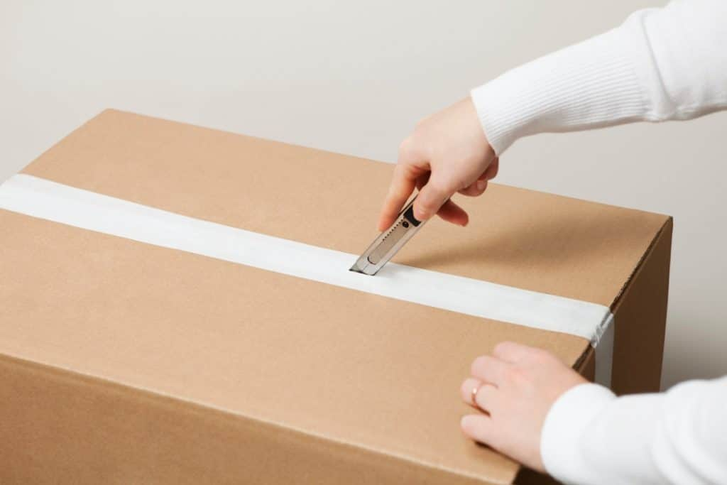Woman opening a cardboard box with a box cutter