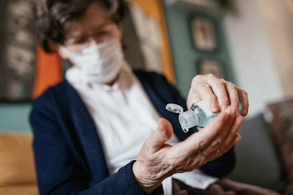 Senior woman using hand sanitizer