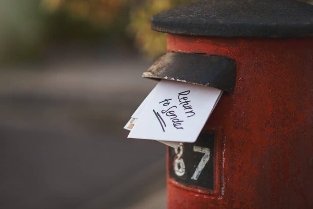 """Mailbox with an envelope sticking out that reads, """"return to sender"""""""