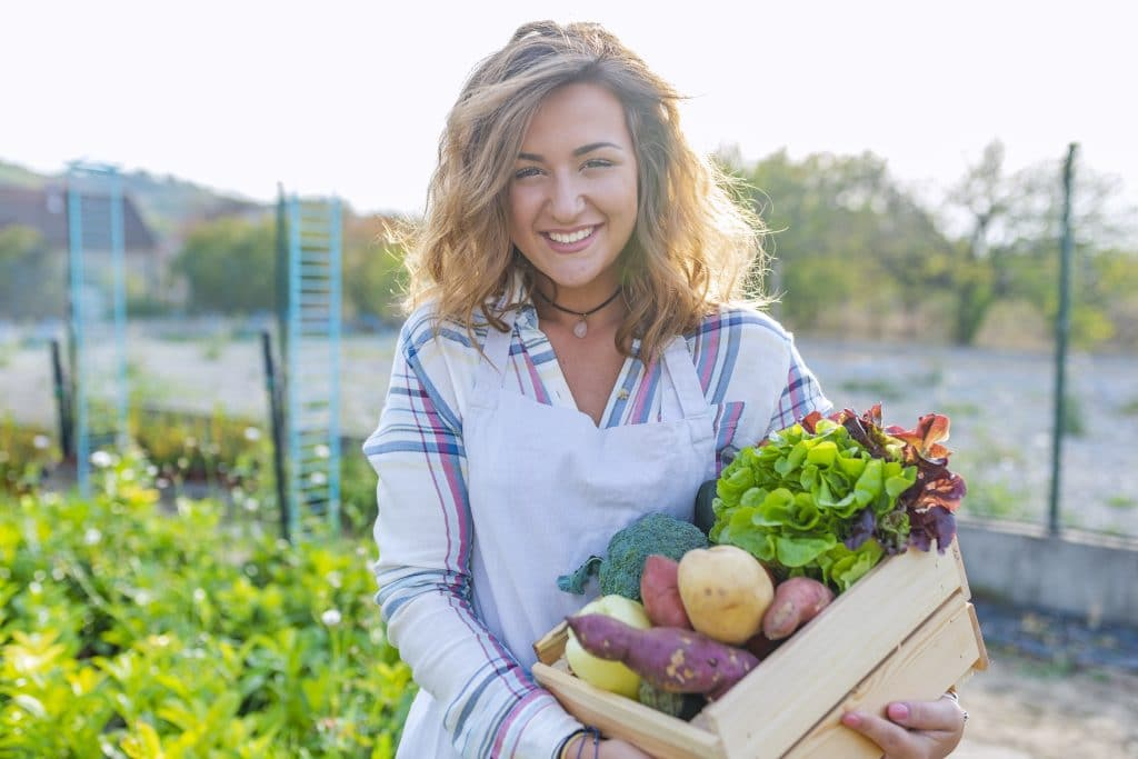Portrait of a girl holding a crate of fresh vegetables.