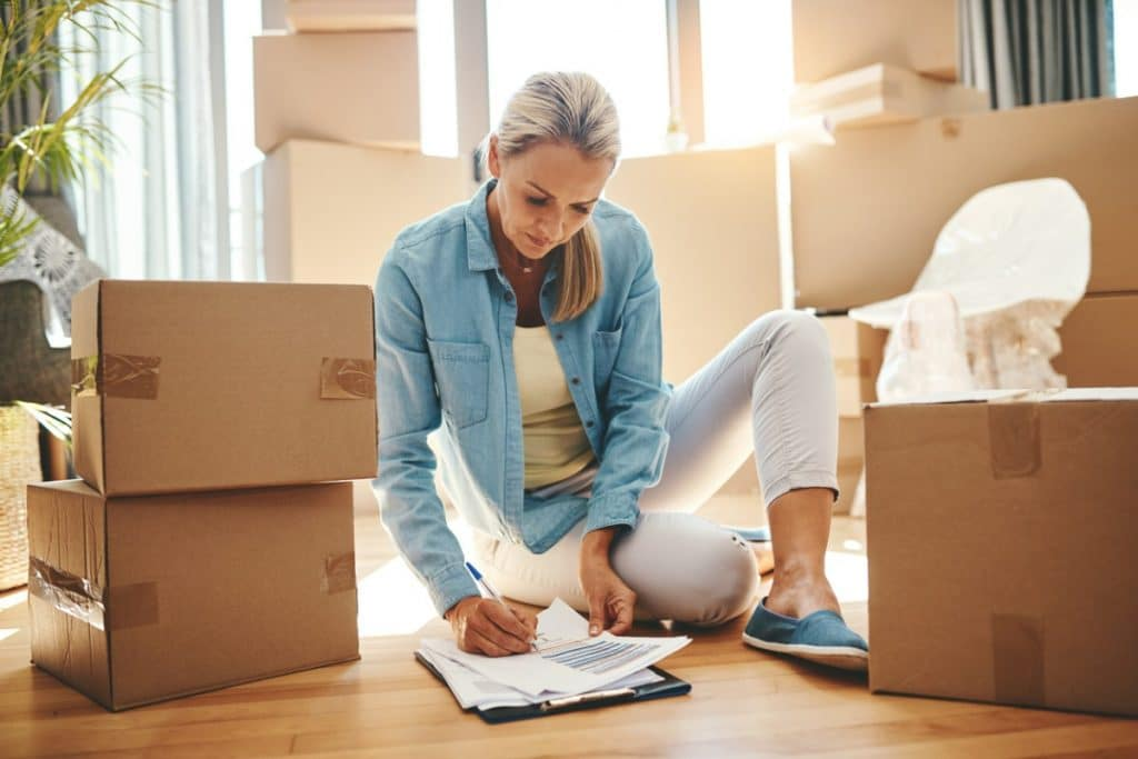 Woman checking off a checklist on the floor of her living room, surrounded by cardboard boxes