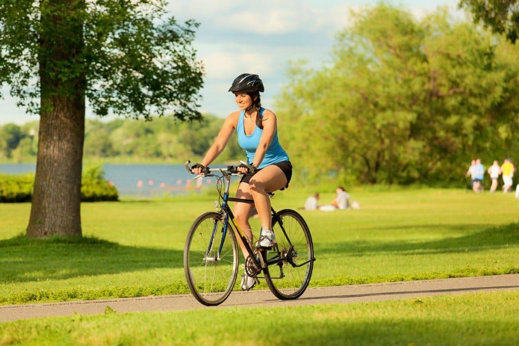 A woman riding her bike alongside a lake.
