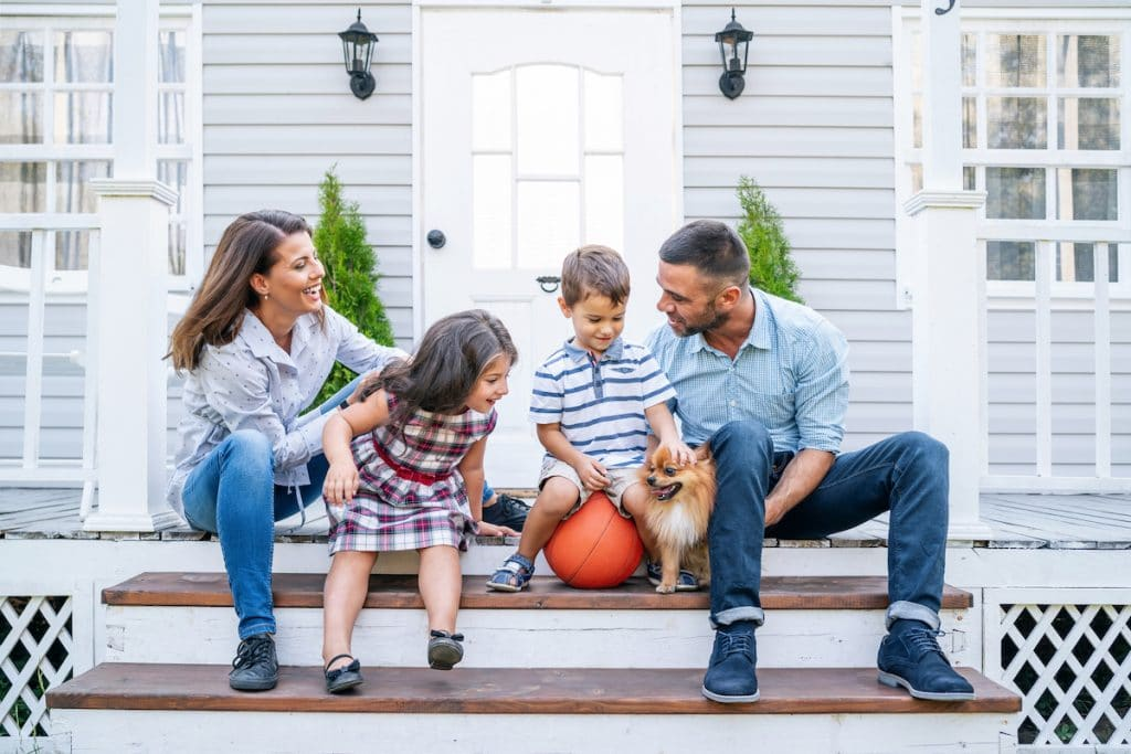 A family and their dog sitting on the porch of their home.