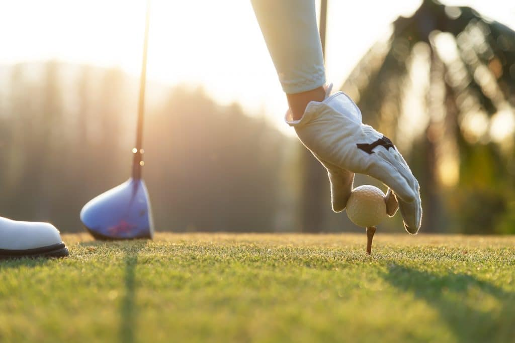 Zoomed in shot of a golfer placing a golf ball on a tee.