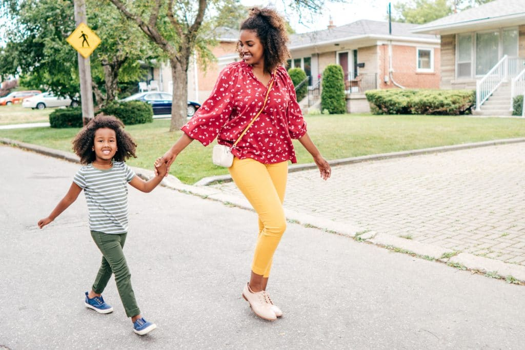 African American mother and daughter holding hands walking through neighborhood.
