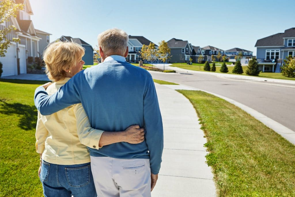 Elderly couple with arms around each other while taking a walk in a neighborhood.